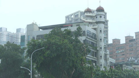 Establishing shot of apartment building and trees in typhoon ビデオ
