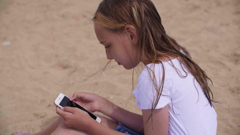 Girl with wet hair sitting on sand and using smartphone Live Action