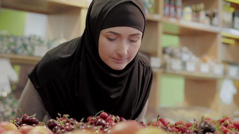 Cute young woman smelling red berries in supermarket. Portrait of pretty young Live Action