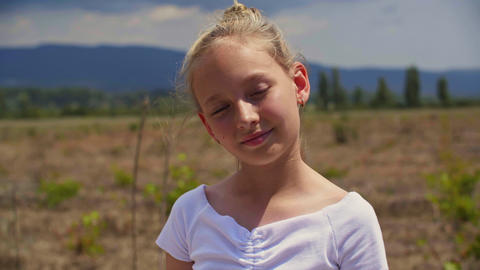 Adorable smiling girl standing on field at sunny summer day Live Action