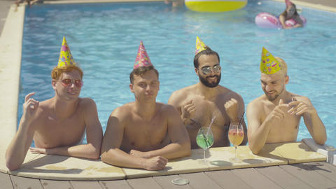 Four positive friends dancing in water at poolside on sunny summer day. Portrait Live Action