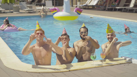 Group of cheerful multiethnic male friends dancing in pool at resort. Portrait Live Action