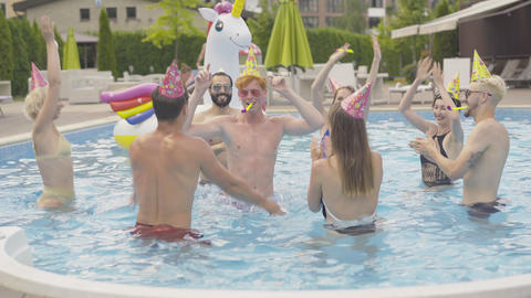 Group of cheerful young people having fun in water pool. Portrait of happy Live Action