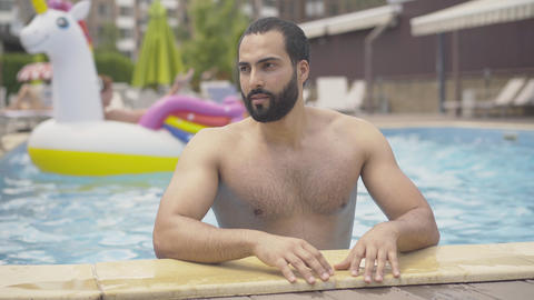 Portrait of handsome young Middle Eastern man posing in pool at luxurious summer Live Action