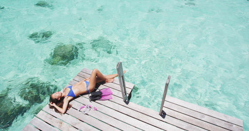 Tropical paradise travel holidays woman enjoying sun lying down sunbathing after Live Action