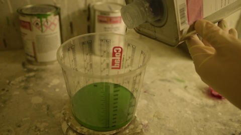 Liquid being poured into a measuring cup with Green Color Live Action