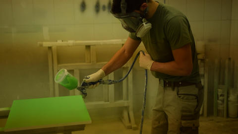 Painter coloring a piece of wood with green color and electric spray paint Live Action