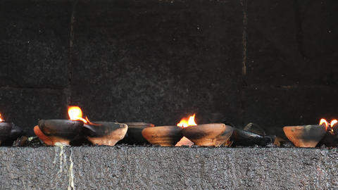 Zooming video of burning oil lamps and incense joss sticks at temple Footage