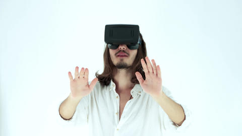 Young man wearing virtual reality headset in Studio Shot. He shows gestures while playing video game Live Action