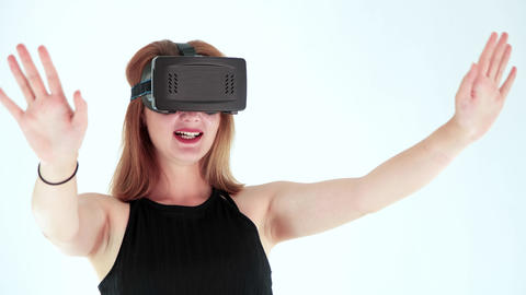 Young woman wearing virtual reality headset in Studio Shot. She shows gestures while playing video Live Action