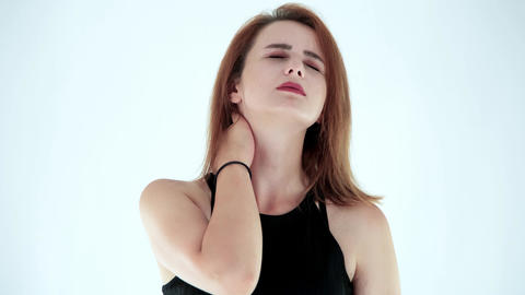 Portrait of tired young woman suffering from neckache and massaging neck isolated on white ライブ動画