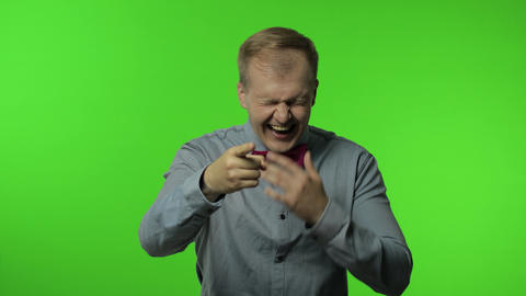 Man pointing finger and laughing out loud, holding belly with hilarious laughter Live Action