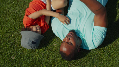 Joyful father and cute son lying on park lawn Live Action