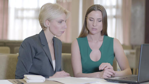 Surprised Caucasian businesswoman discussing project with colleague in cafe Live Action