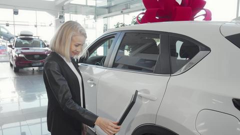 Cheerful woman choosing new car at dealership salon Live Action