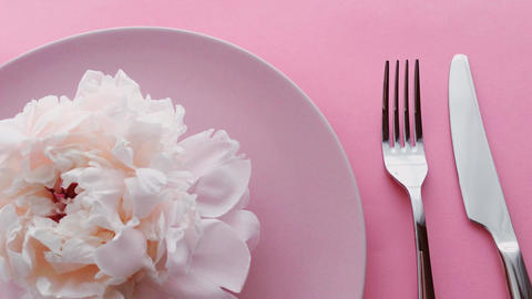 Pink table setting with peony flowers on plate and silverware for luxury dinner Live Action