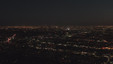 AERIAL: Slow flight over Hollywood Hills at Night with view on Downtown Los Live Action