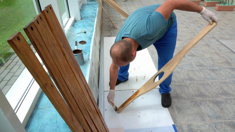 Carpenter polishing wooden plank with lacquer. Worker polish wood board Live Action