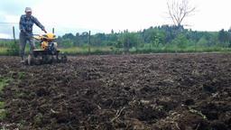 Man plowing field using a cultivator, garden preparation Footage