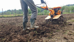 Man plowing field with cultivator, garden preparation Footage