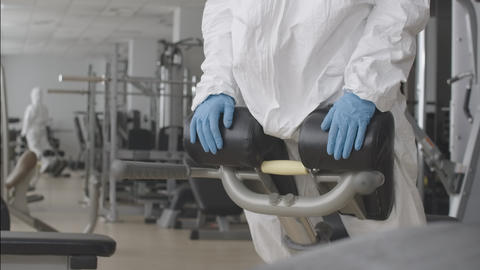 Sportswoman in protective suit and respirator training back muscles on equipment Live Action