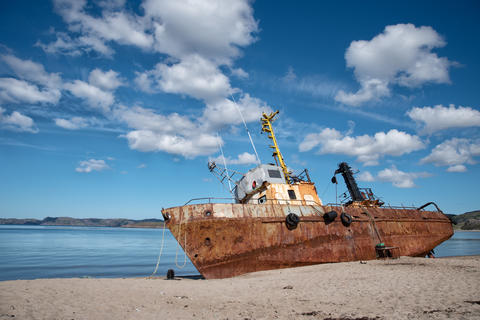 Bright rusty old abandoned fishing boat on the coast フォト