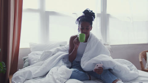 Attractive Young African American Woman sits in bed, drinks morning coffee and Live Action