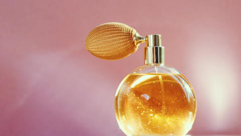 Luxury golden perfume bottle and shining light flares on pink background Live Action