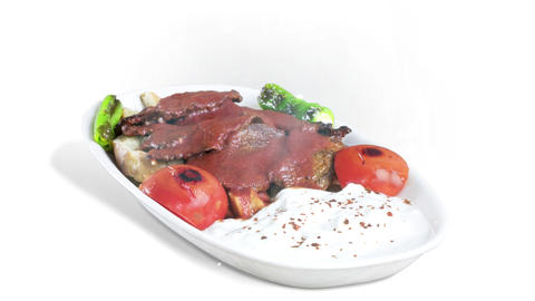 Turkish traditional Iskender Kebab on White Plate on white background Live Action