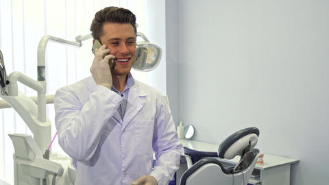 Dentist uses his cellphone at the office Live Action