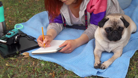 Girl laying on a lawn and writing, her pug laying beside Live Action