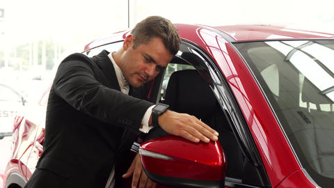 A cheerful salesman points to the excellent quality of the car Live Action