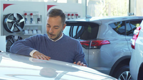 Business man examines the car in the car showroom Live Action