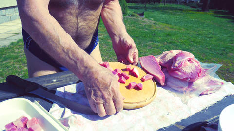 Man is slicing pork meat on piece. Cooking outside in the garden. Pork meat on a cutting board Live Action