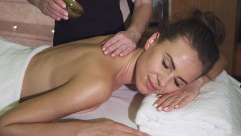 A professional masseuse pours a beautiful customer with oil and massage her Live Action