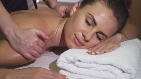 Close-up shows the relaxed face of a girl who is having a back massage Live Action