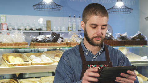 Handsome professional male baker using digital tablet at his store Live Action