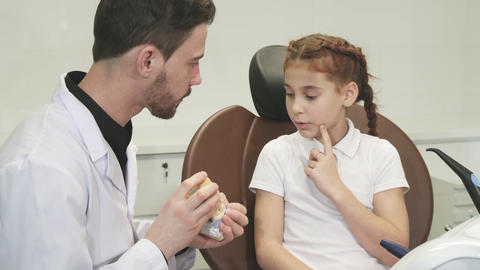 A smart doctor tells a little girl about the structure of the human jaw Live Action