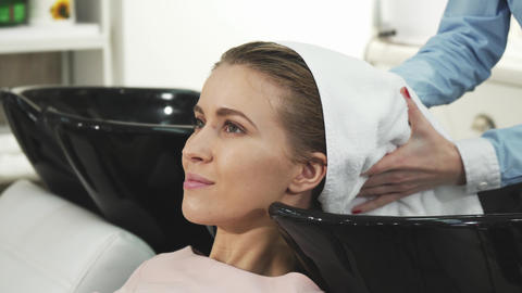 Beautiful woman smiling getting her hair dried by a professional hairdresser Live Action