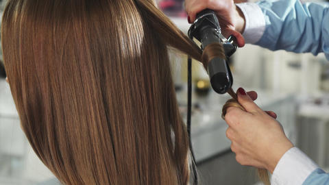 Rearview close up of a woman getting her hair curled by a professional hairstylist Live Action