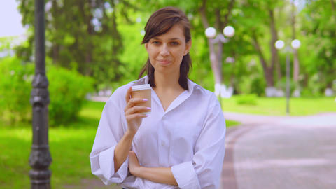 young female in white shirt drinking coffee walk on the street in summer season Live Action