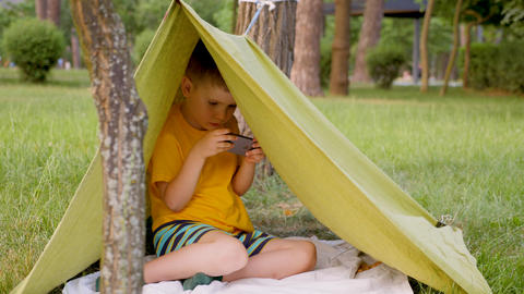 Young traveler in tent playing video game. Traveling concept. Boy in hand made Live Action