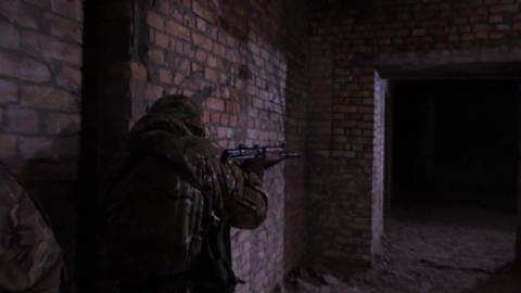 Fully equipped, armed soldier during a reconnaissance mission in an unfinished Live Action