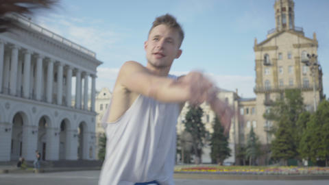 Middle shot portrait of cheerful young man dancing at sunrise on city square Live Action