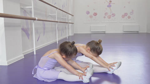 Cute little ballerinas stretching together at dancing school together Live Action