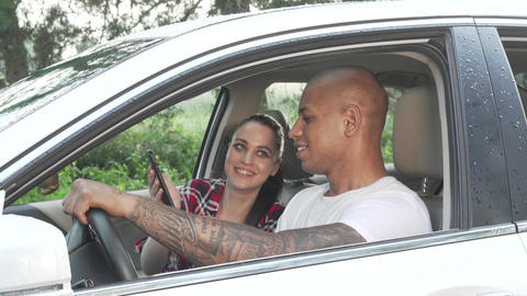 Young multiracial couple using smart phone in their car during road trip Live Action