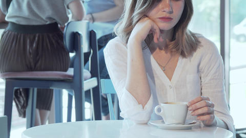 Sad woman sitting alone at the coffee shop Live Action