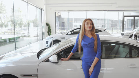 Attractive elegant woman looking away dreamily standing near new car Live Action