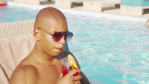Relaxed handsome African man sipping his cocktail by the swimming pool Live Action