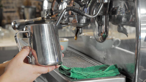 Barista steaming milk in frothing pitcher preparing drinks for coffee shop customers Live Action